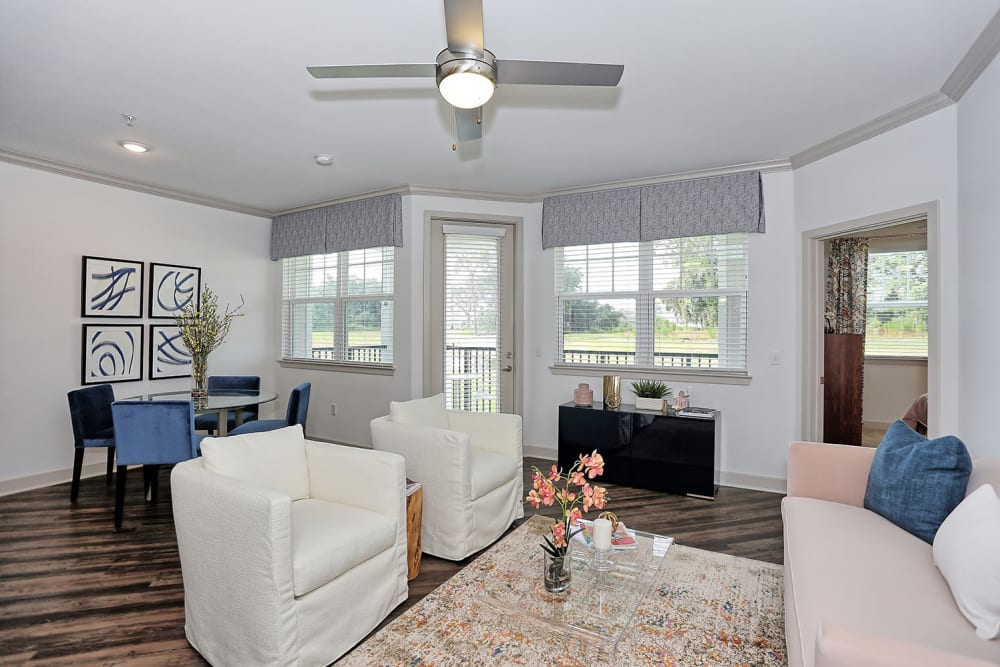 Ceiling fan and beautiful hardwood floors in the well-furnished living area of a model home at The Slate in Savannah, Georgia