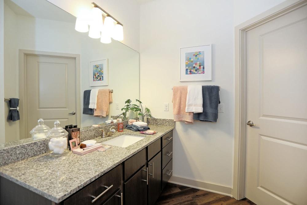 Granite countertop and a large vanity mirror in a model home's bathroom at The Slate in Savannah, Georgia