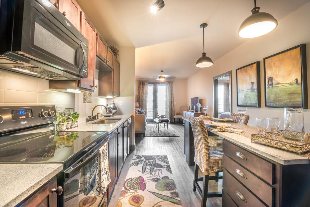 Spacious open-concept gourmet kitchen with granite countertops in a model apartment at Union At Carrollton Square in Carrollton, Texas