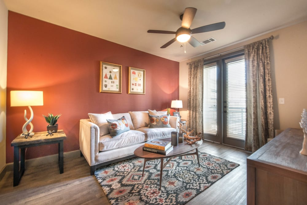 Accent wall and a ceiling fan in the living area of a model apartment at Union At Carrollton Square in Carrollton, Texas