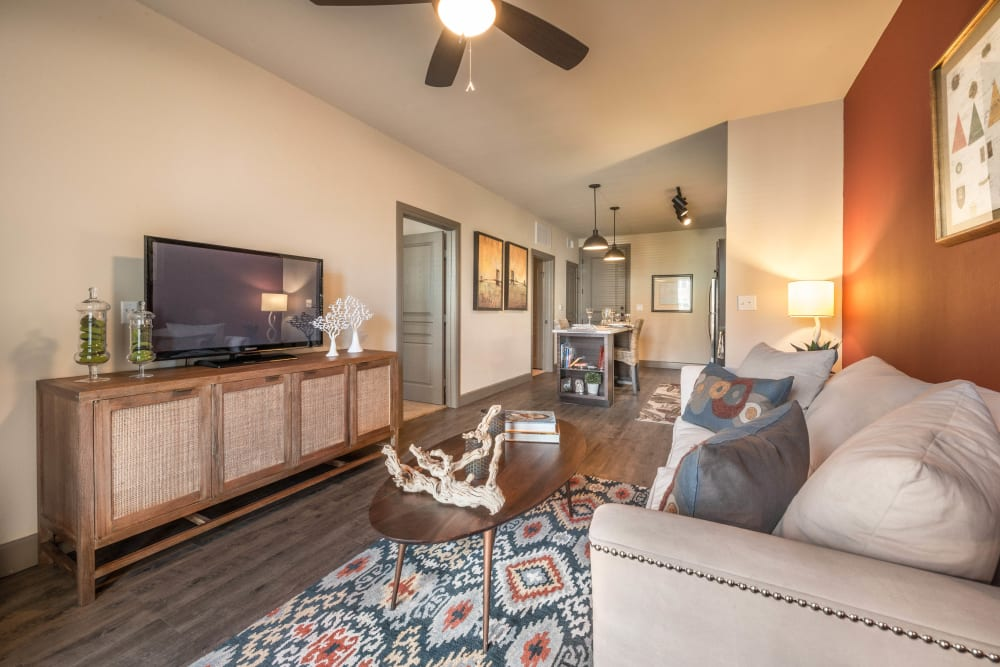Well-furnished living area with a ceiling fan in a model home at Union At Carrollton Square in Carrollton, Texas