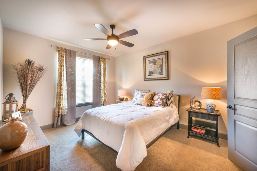 Modern furnishings and a ceiling fan in a model home's bedroom at Union At Carrollton Square in Carrollton, Texas