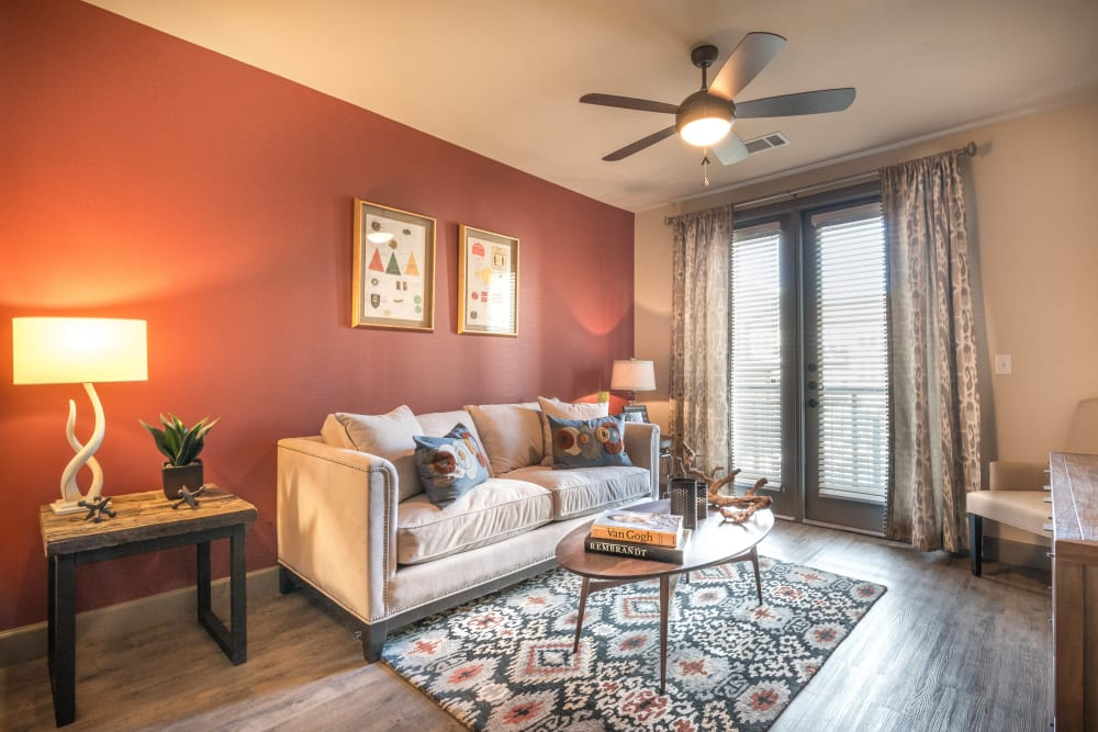Accent wall and a ceiling fan in a model home's living area at Union At Carrollton Square in Carrollton, Texas