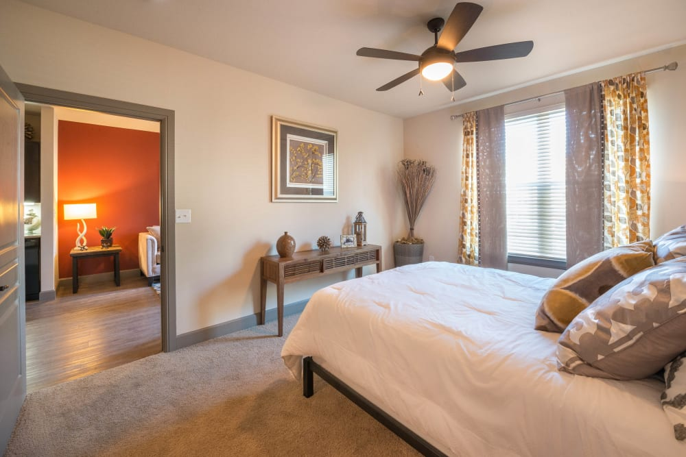 Model home's master bedroom with a ceiling fan and plush carpeting at Union At Carrollton Square in Carrollton, Texas