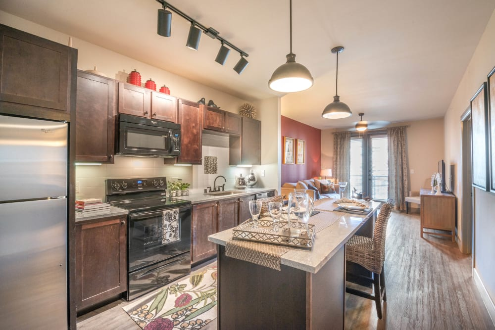 Gourmet kitchen with an island and granite countertops in a model home at Union At Carrollton Square in Carrollton, Texas