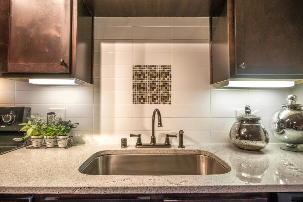 Custom tile backsplash and a recessed sink in a model apartment's gourmet kitchen at Union At Carrollton Square in Carrollton, Texas