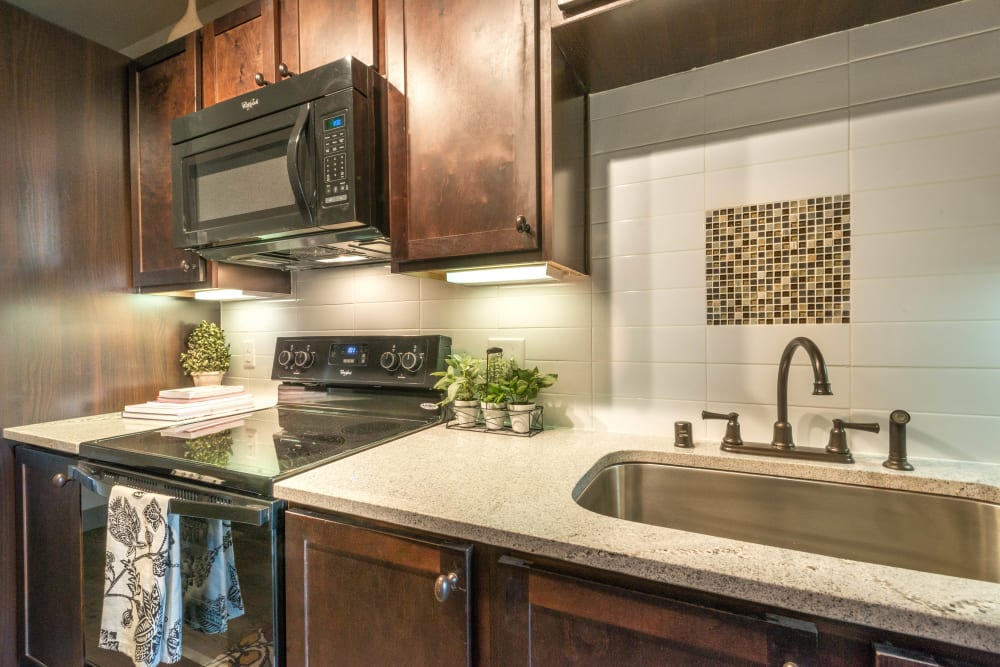 Granite countertops and sleek black appliances in a model home's gourmet kitchen at Union At Carrollton Square in Carrollton, Texas