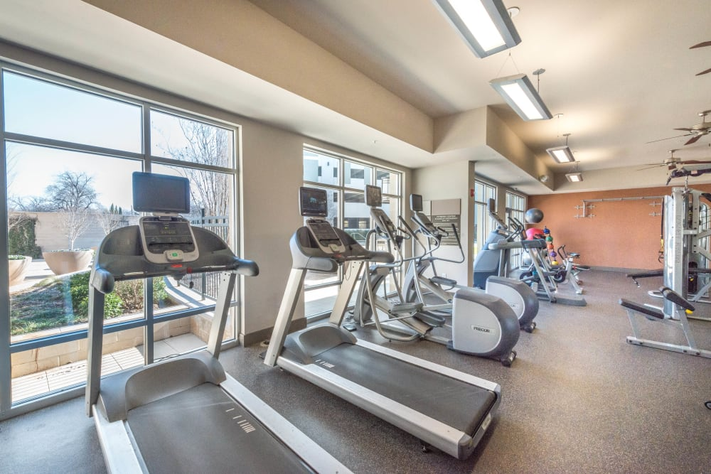 Treadmills and other cardio equipment in the fitness center at Union At Carrollton Square in Carrollton, Texas