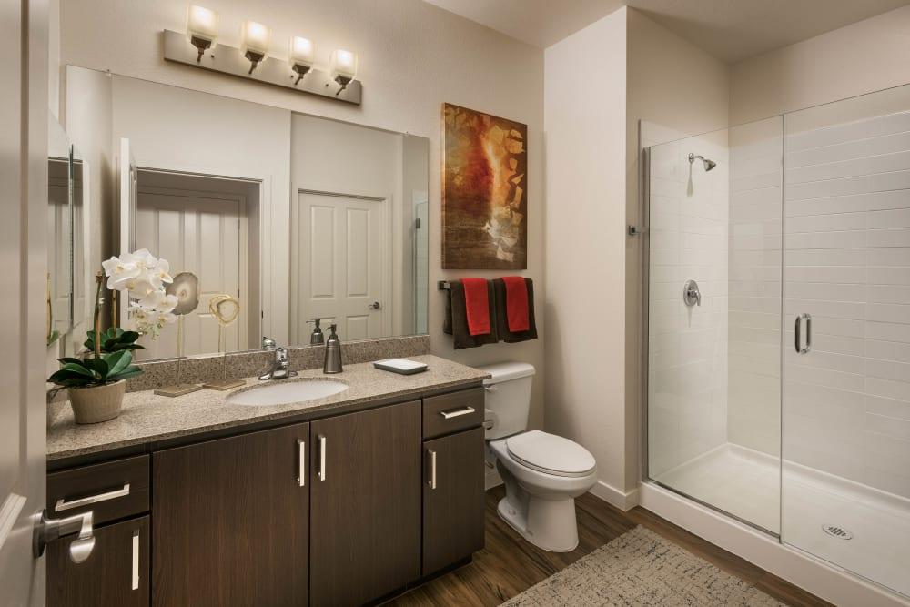 Tiled stand-up shower and a granite countertop in a model apartment's bathroom at Vistara at SanTan Village in Gilbert, Arizona