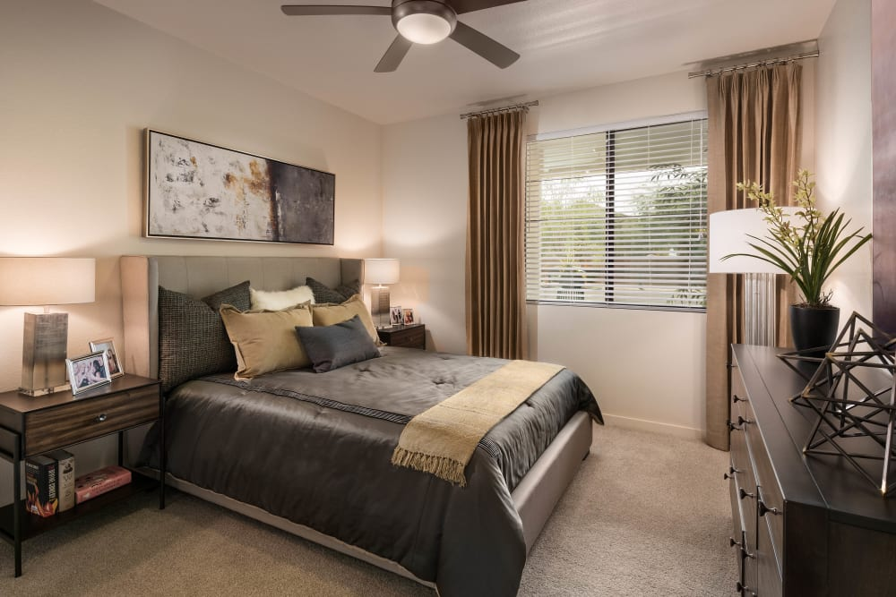 Well-furnished model home's bedroom with a ceiling fan at Vistara at SanTan Village in Gilbert, Arizona