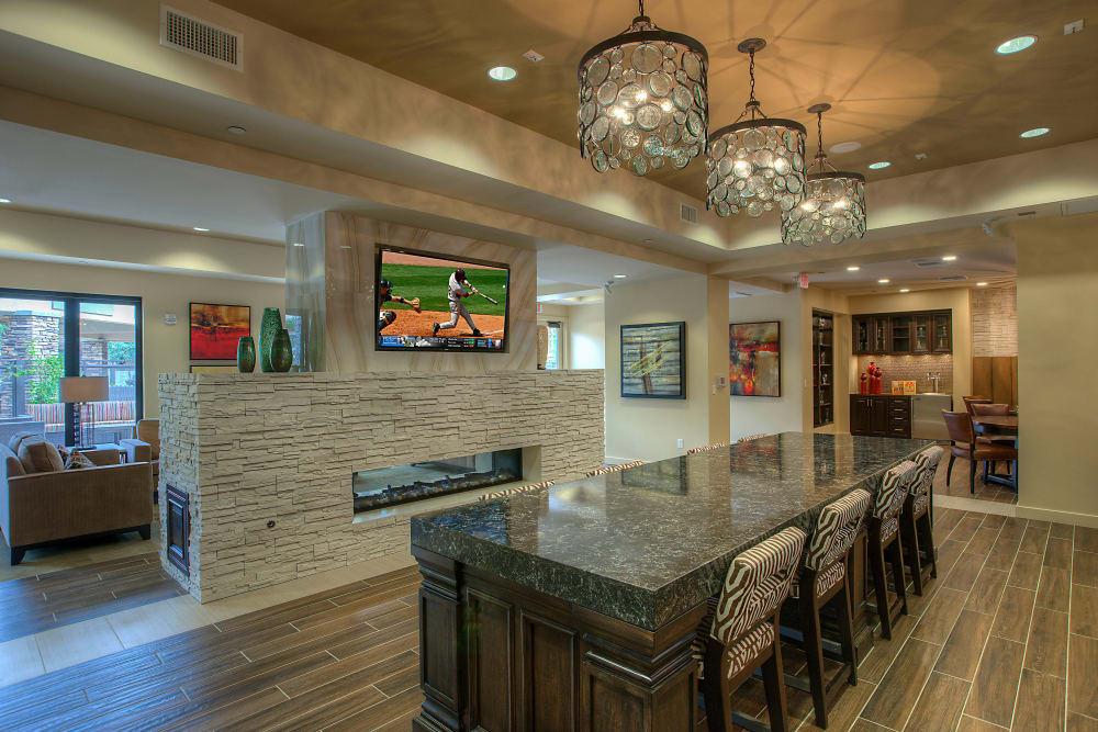 Clubhouse lounge with bar seating and flatscreen TVs at Vistara at SanTan Village in Gilbert, Arizona