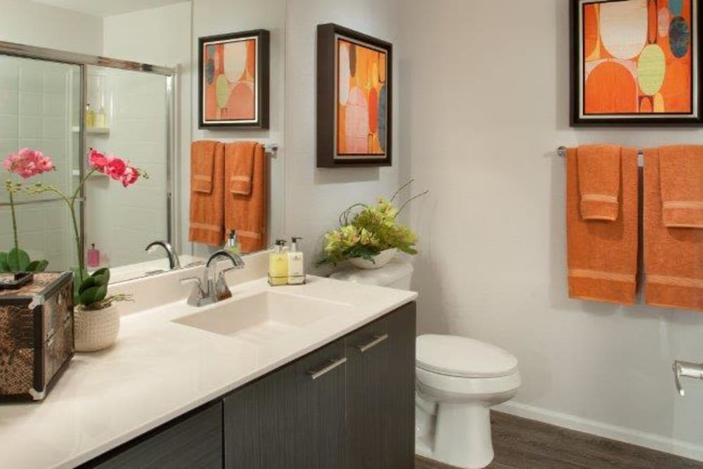 Model home's bathroom with a large vanity mirror and a quartz countertop at Vive in Chandler, Arizona