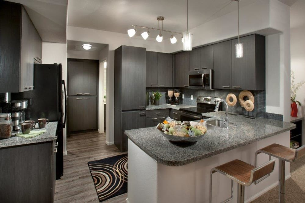 Gourmet kitchen with an island and granite countertops in a model home at Vive in Chandler, Arizona