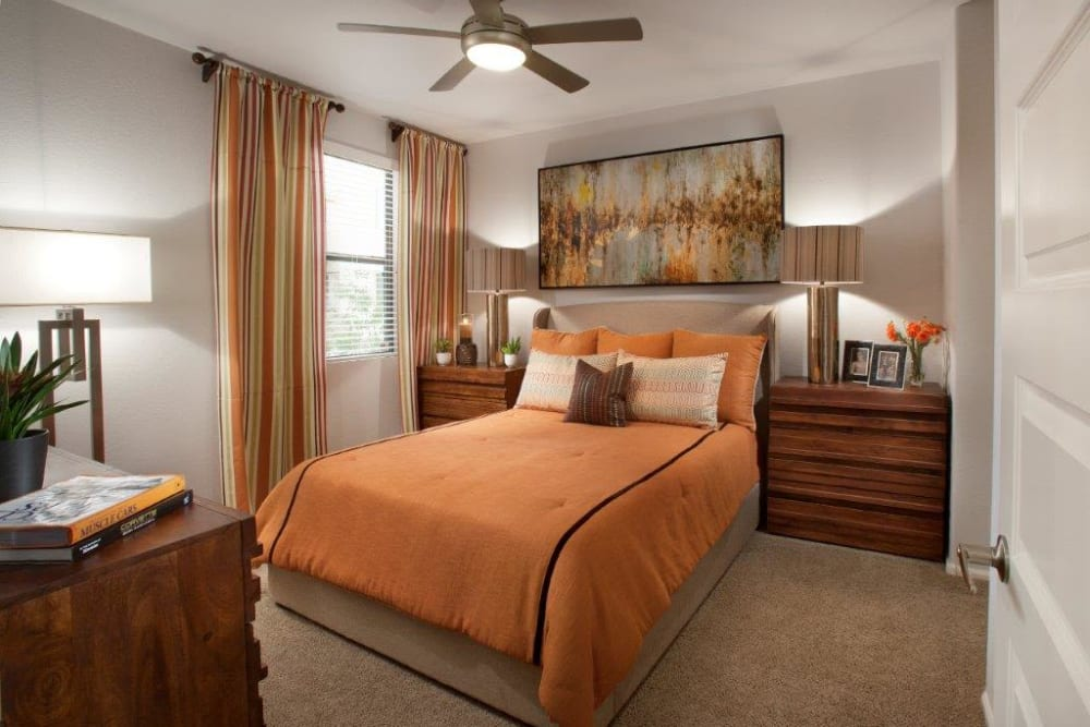 Model home's well-furnished master bedroom with a ceiling fan at Vive in Chandler, Arizona