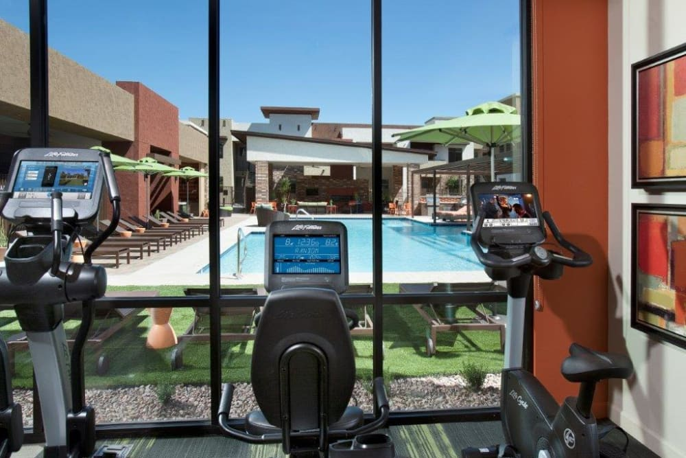View of the swimming pool from the cardio machines in the fitness center at Vive in Chandler, Arizona