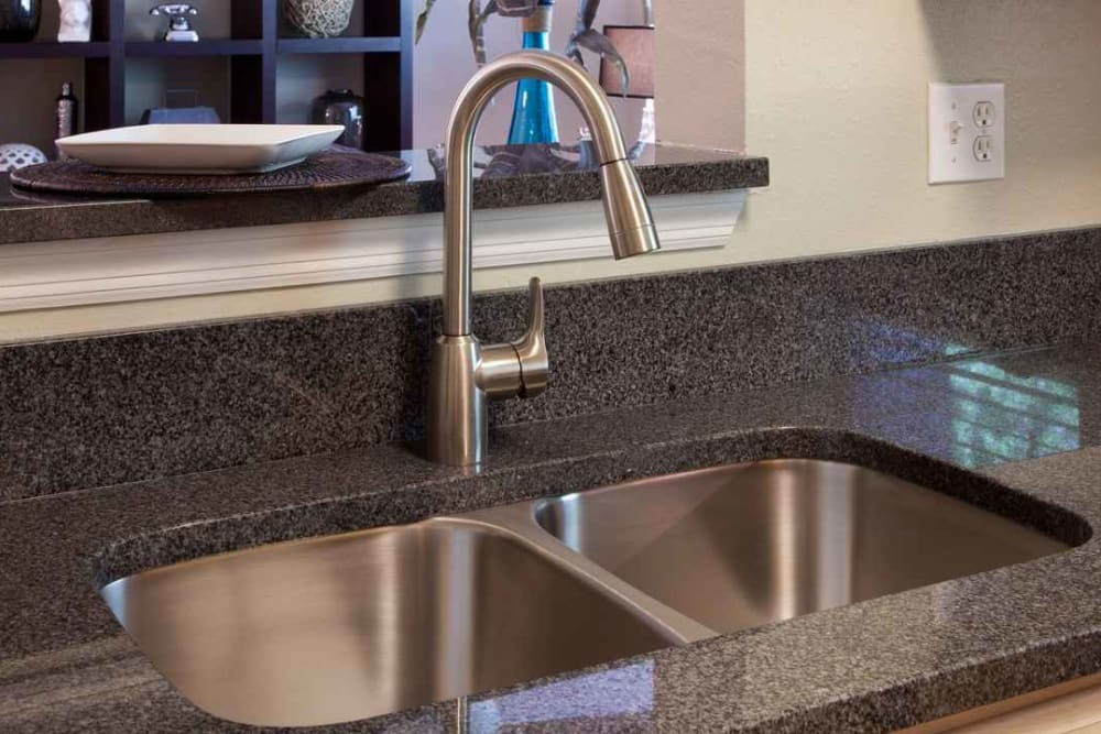 Granite countertops and a dual-basin sink in a model home at Wimberly at Deerwood in Jacksonville, Florida