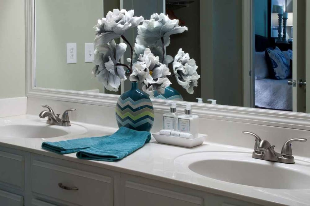 Large vanity mirror and quartz countertops in a model home's bathroom at Wimberly at Deerwood in Jacksonville, Florida