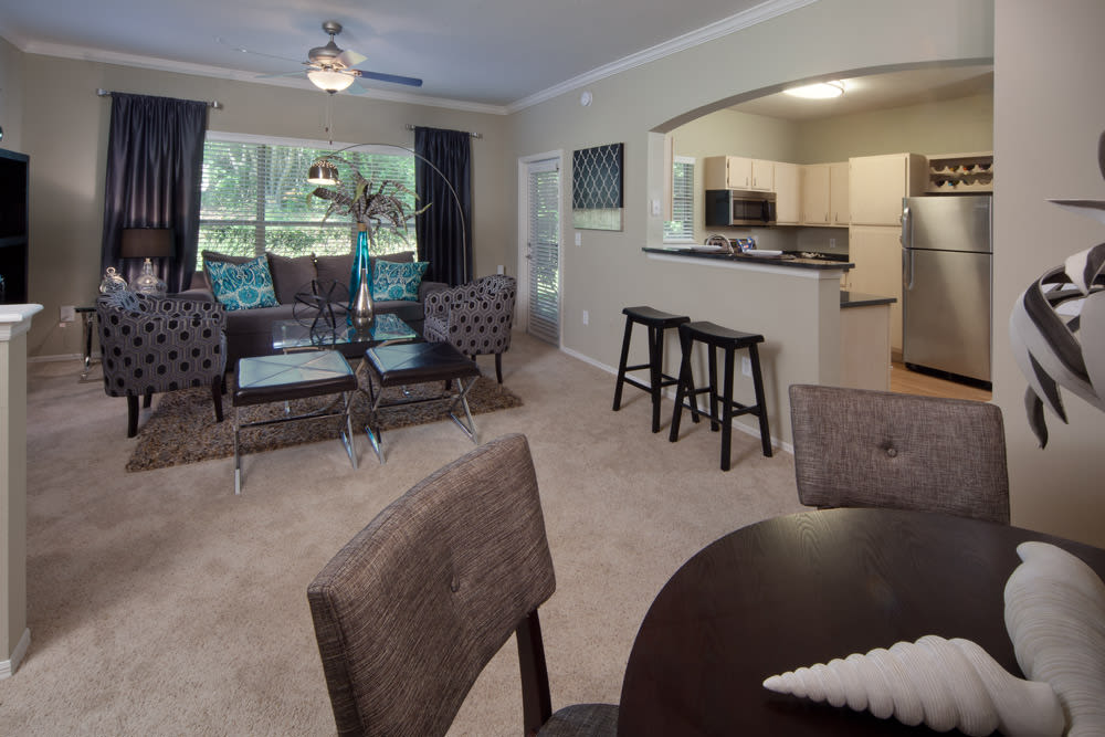 Open-concept model home with plush carpeting throughout the living areas at Wimberly at Deerwood in Jacksonville, Florida