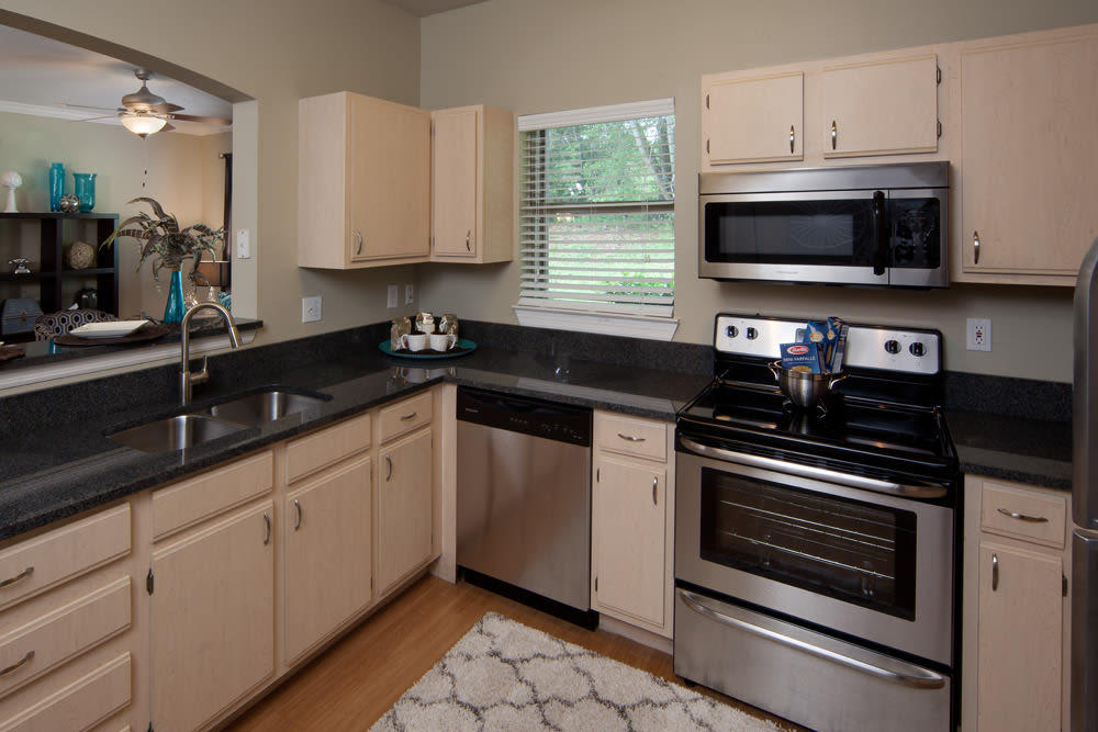 Model apartment's gourmet kitchen with granite countertops at Wimberly at Deerwood in Jacksonville, Florida