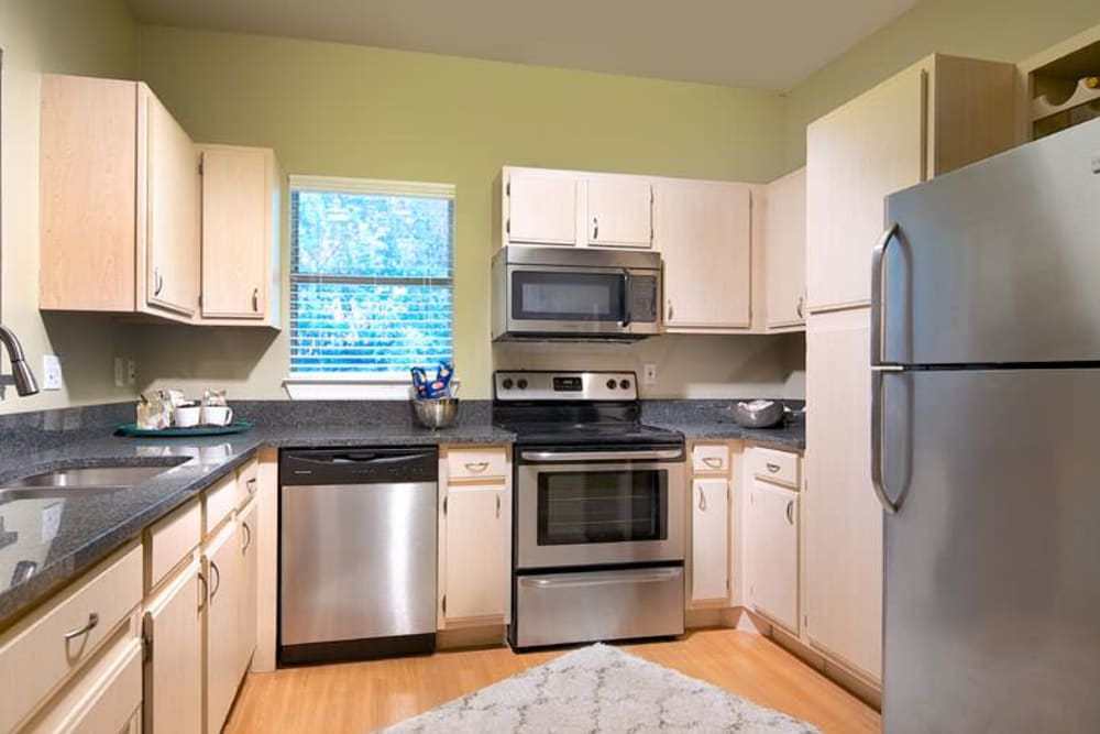 Light wood cabinetry and stainless-steel appliances in a model home's kitchen at Wimberly at Deerwood in Jacksonville, Florida
