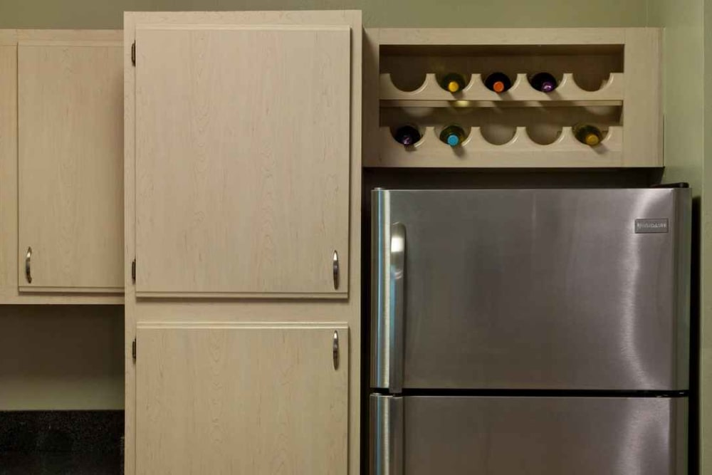 Pantry cupboards and a built-in wine rack above the stainless-steel refrigerator in a model home at Wimberly at Deerwood in Jacksonville, Florida