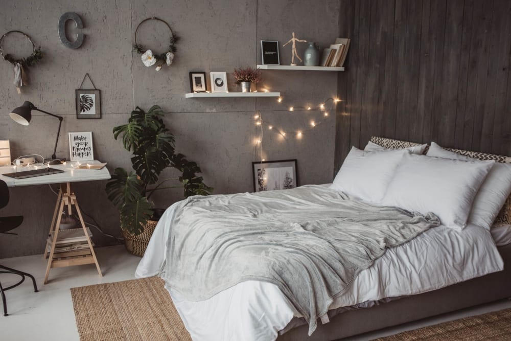 Well-furnished bedroom in a model home at Olympus Court Apartments in Bakersfield, California