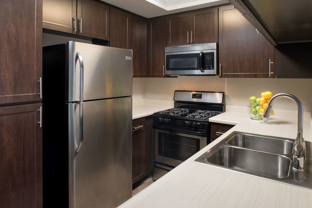 Kitchen with stainless-steel appliances and wood-style cabinets at Shadow Ridge Apartment Homes in Simi Valley, California