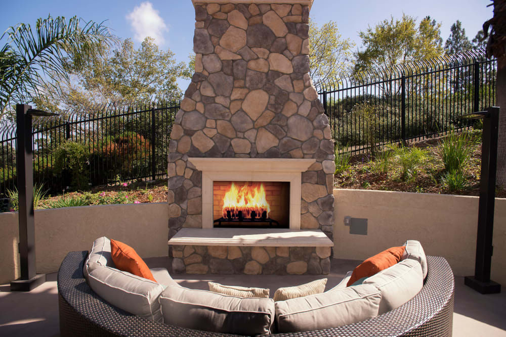 Comfortable outdoor couch next to a fireplace at Shadow Ridge Apartment Homes in Simi Valley, California