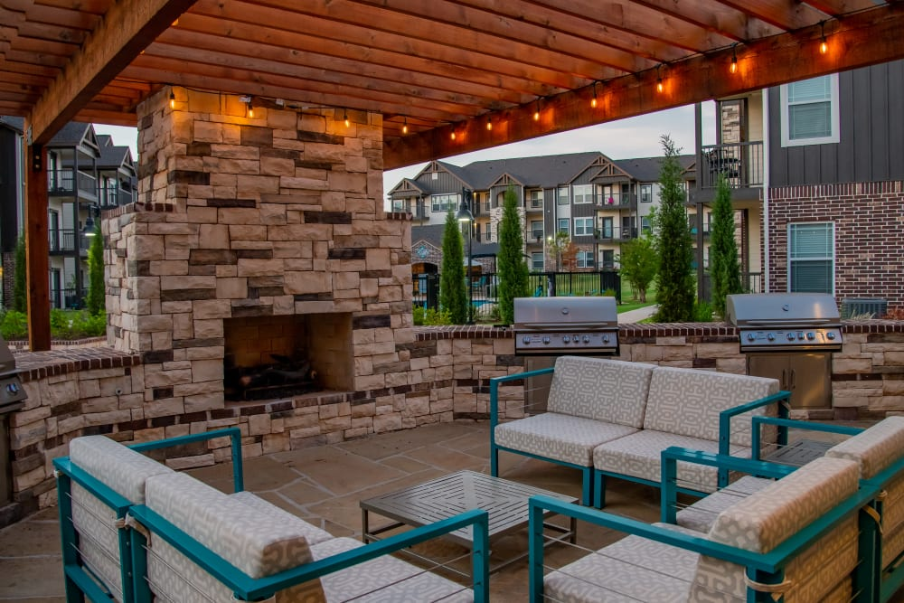 Outdoor lounge with a fireplace at Bend at New Road Apartments in Waco, Texas