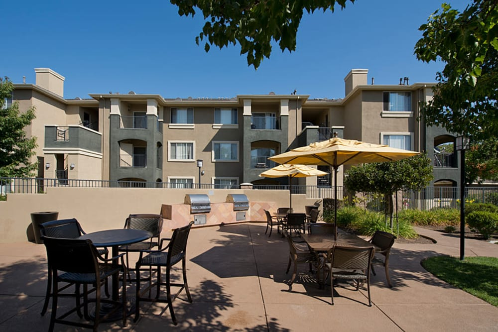 Barbecue grill with tables and chairs for enjoying a nice outdoor dinner at Cross Pointe Apartment Homes in Antioch, California