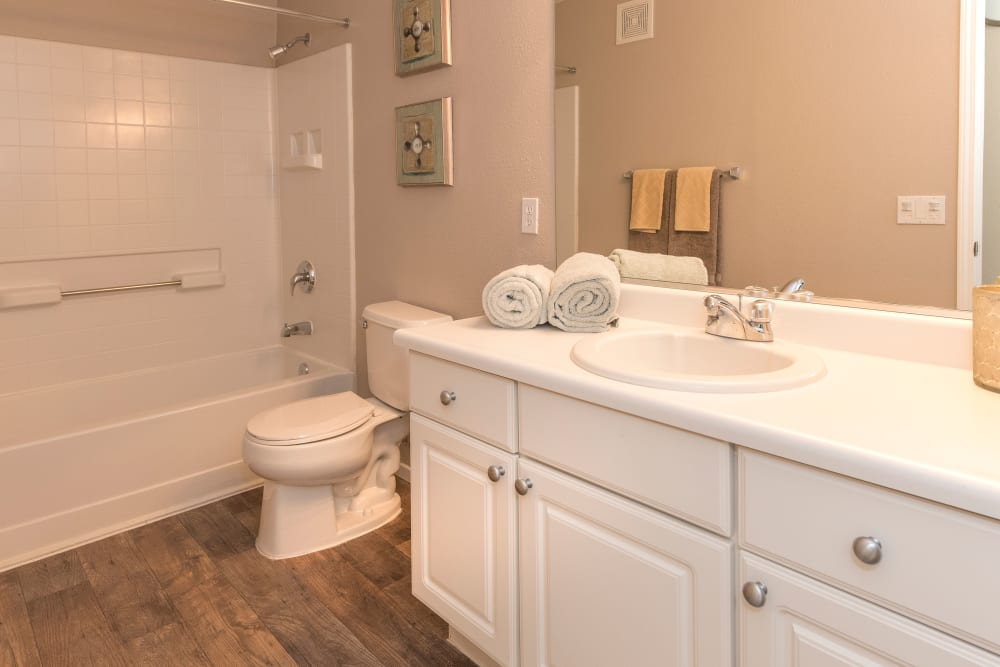 Bathroom with plenty of cabinet space and a large vanity mirror at Cross Pointe Apartment Homes in Antioch, California