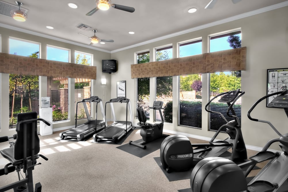 Fitness center with large windows at Cross Pointe Apartment Homes in Antioch, California