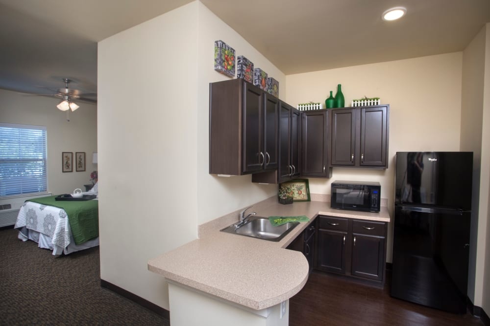 View of kitchen and bedroom in small apartment at The Claiborne at Thibodaux in Thibodaux, Louisiana