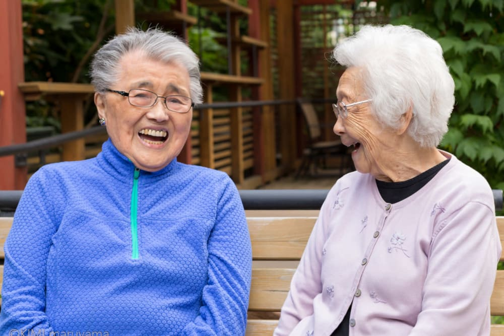 Two residents having a laugh on a bench near Nikkei Manor in Seattle, Washington