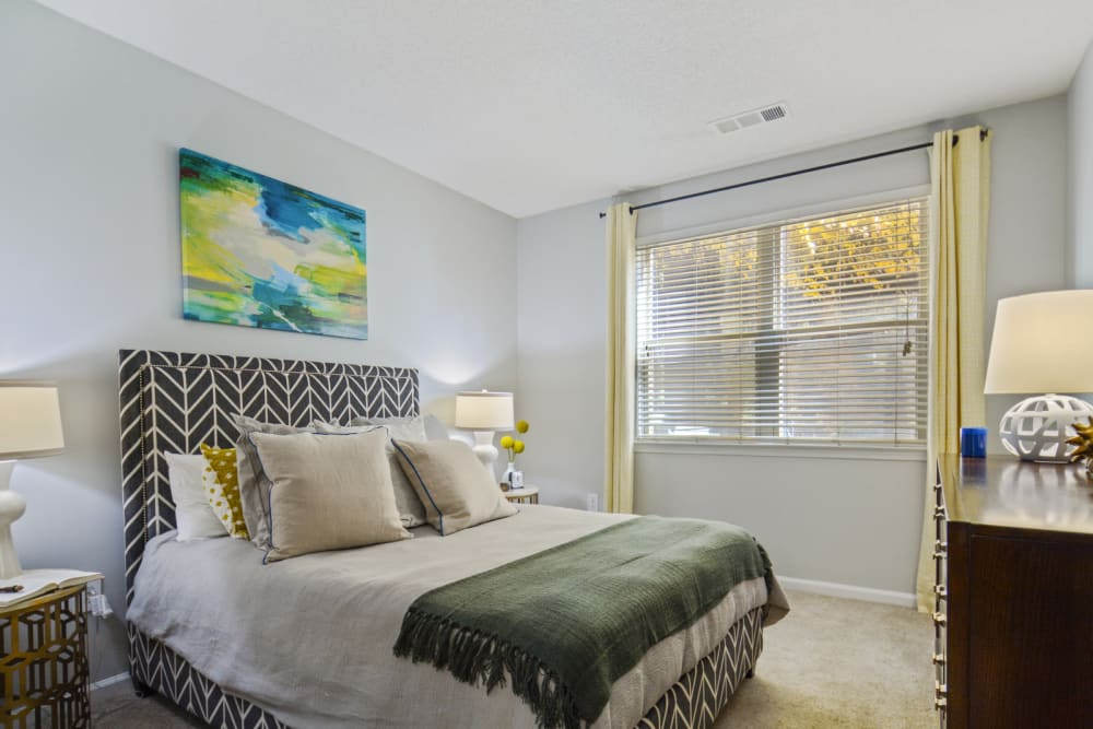Draped bay window and modern furnishings in a model home's bedroom at Ellington Midtown in Atlanta, Georgia
