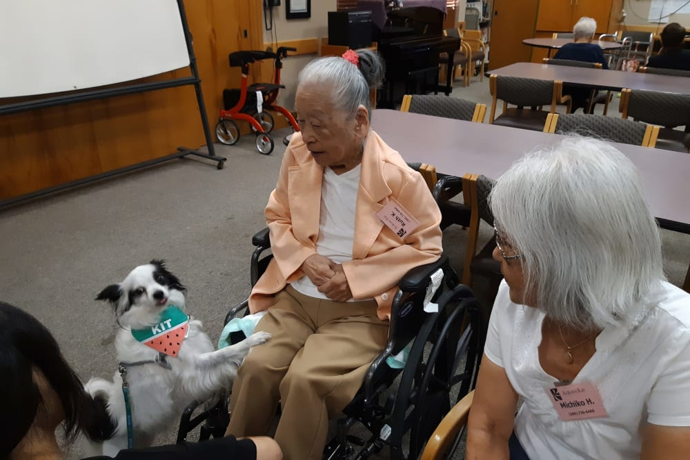 Two residents and a small dog at Nikkei Manor in Seattle, Washington