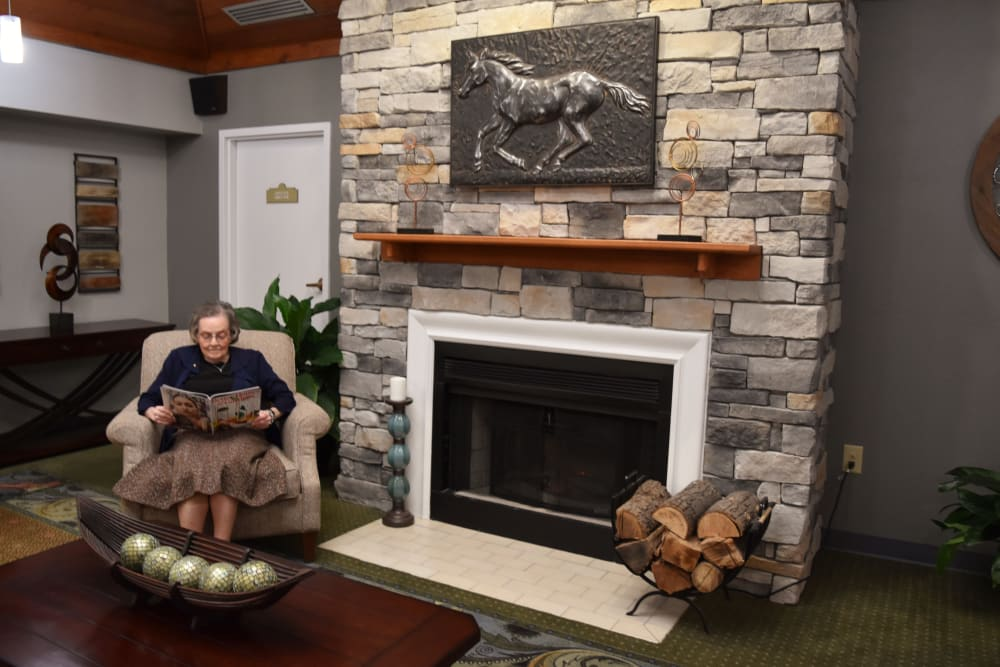 Resident relaxes with a magazine by the fireplace at Willow Creek Senior Living in Elizabethtown, Kentucky.