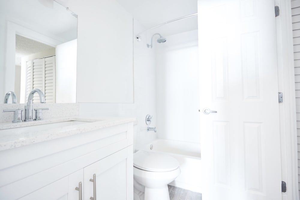 Large vanity mirror in well-lit bathroom of model home at Aliro in North Miami Beach, Florida