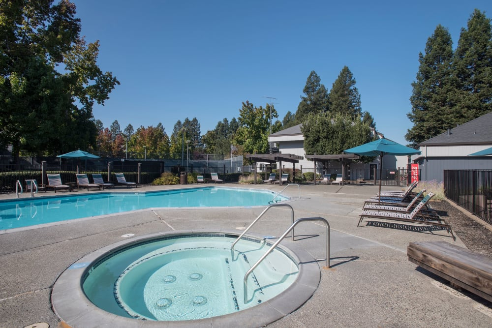 Spacious sundeck with table and chairs next to a swimming pool at Park Ridge Apartment Homes in Rohnert Park, California