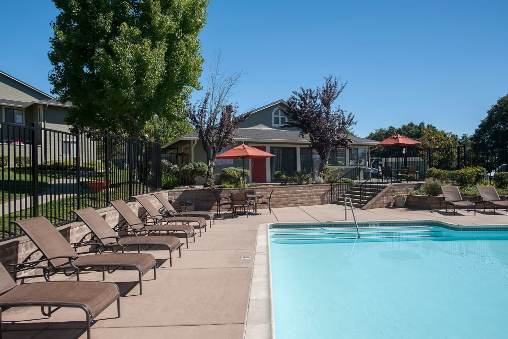 Swimming pool with a sundeck and lounge chairs at Ridgecrest Apartment Homes in Martinez, California