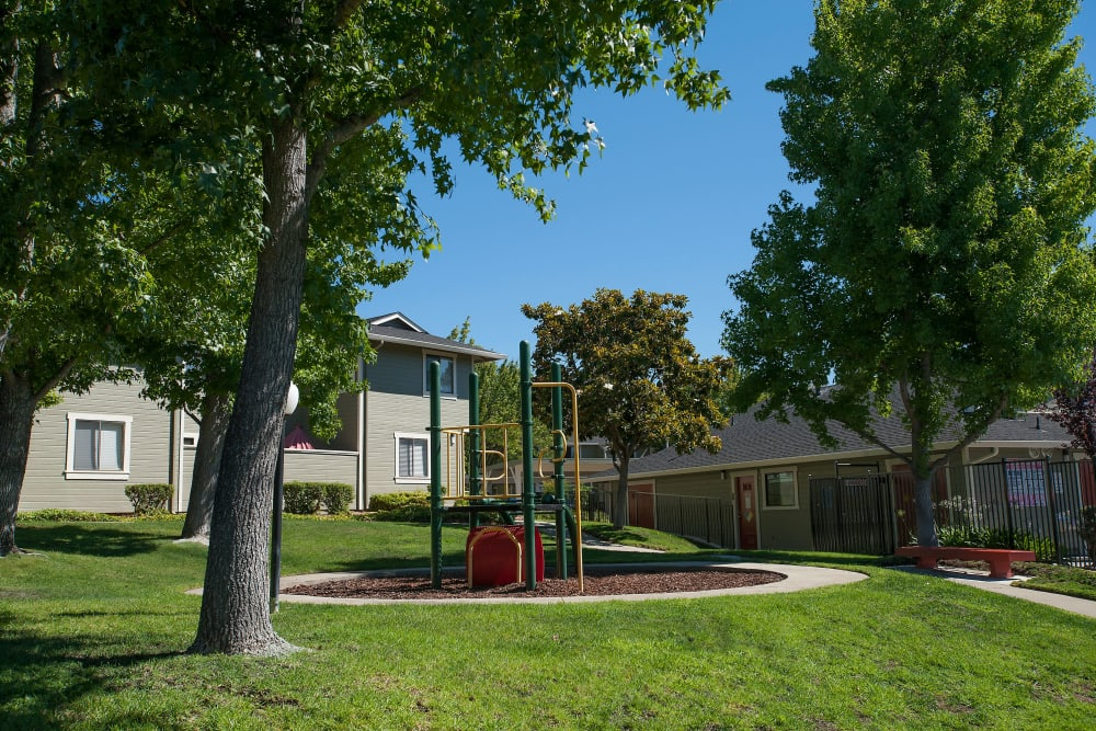A children's playground surrounded by grass at Ridgecrest Apartment Homes in Martinez, California