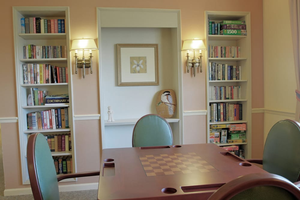 A library with a small table and chairs at Sunset Lake Village Senior Living in Venice, FL