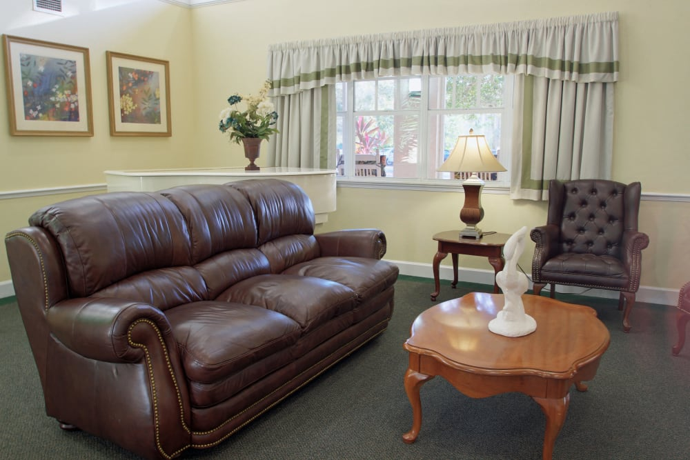 A large room with leather couch at Sunset Lake Village Senior Living in Venice, FL