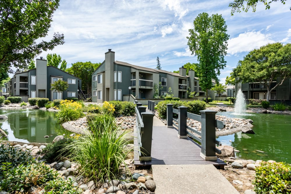 Pond and exterior of buildings at Waterfield Square Apartment Homes in Stockton, California