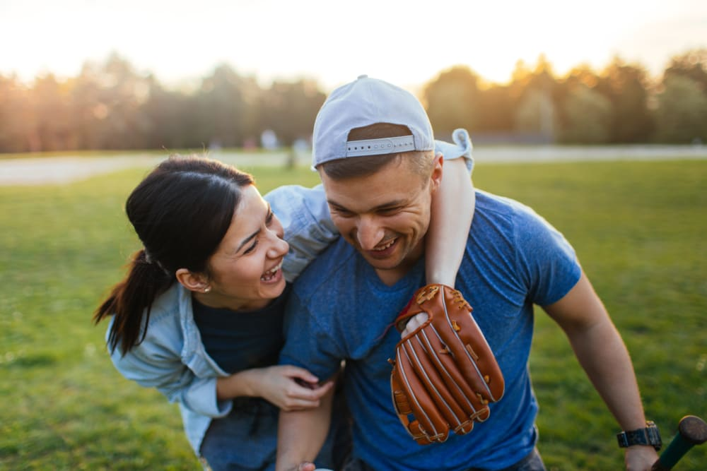 Couple playing baseball together near UNCOMMON Raleigh in Raleigh, North Carolina