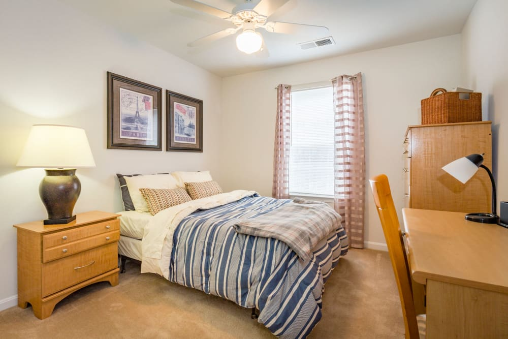 Comfortable model bedroom and large window at Sunchase at Longwood in Farmville, Virginia