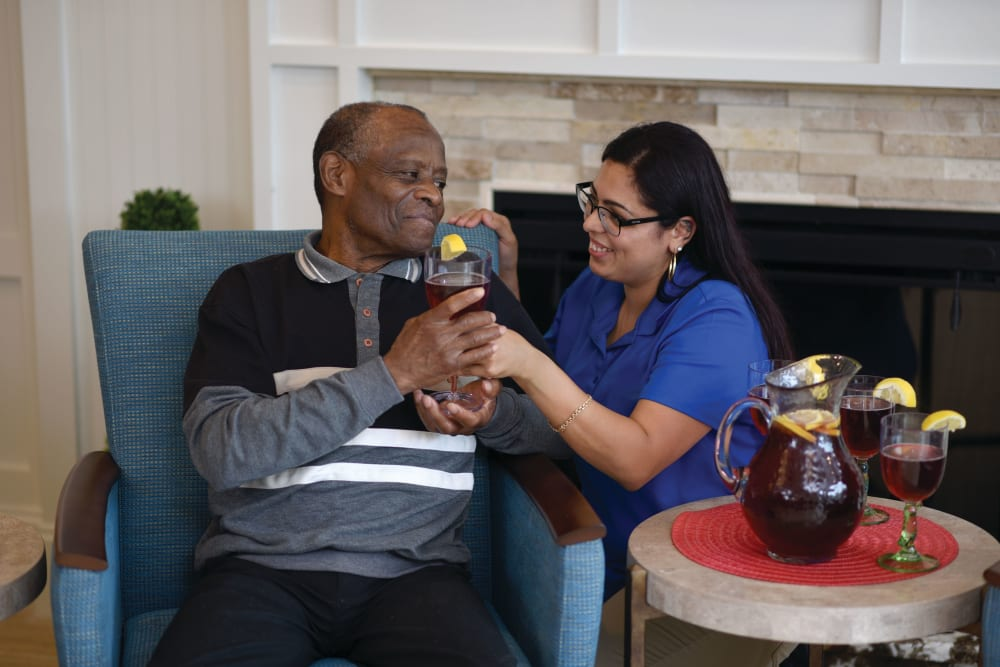 Caregiver handing drink to senior man at Symphony at Valley Farms in Louisville, Kentucky