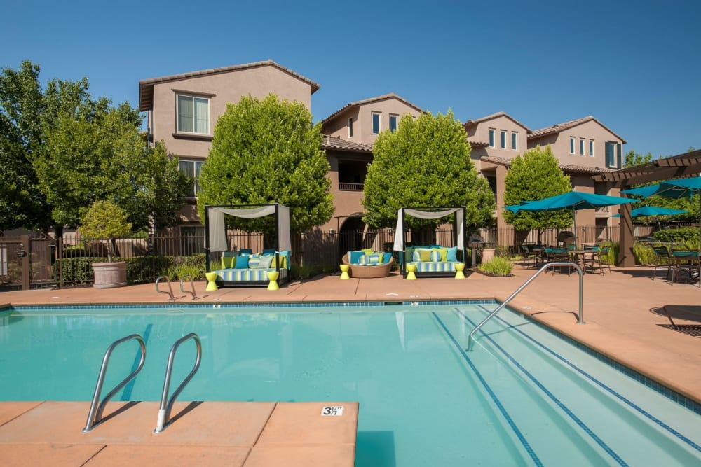 Large swimming pool with a sundeck and lounge chairs at Venu at Galleria Condominium Rentals in Roseville, California