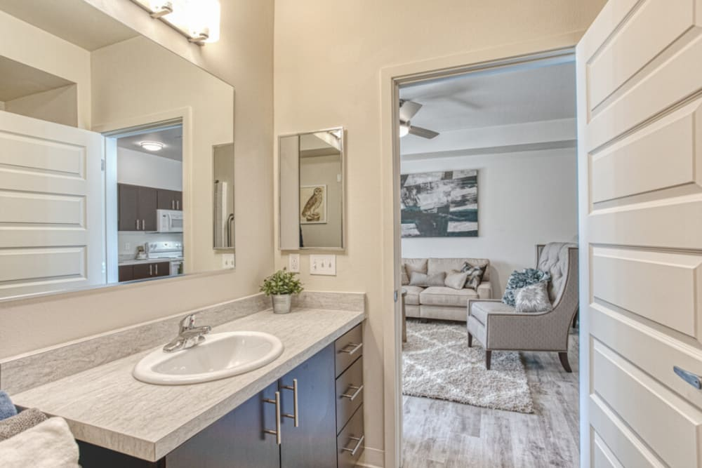 Model bathroom with a view of the living room at LARC at Burien in Burien, Washington