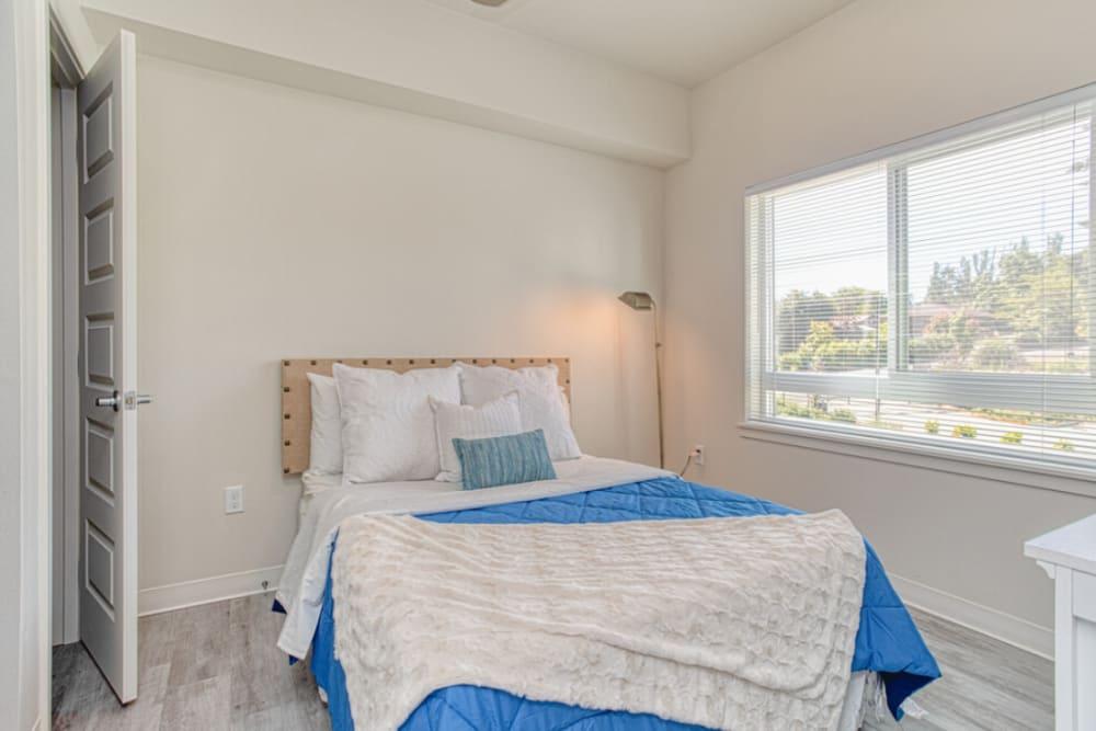 Well lit model bedroom at LARC at Burien in Burien, Washington